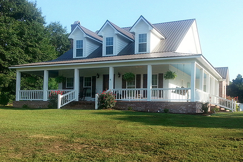 Comfortable southern country cottage house with wrap around porch by Arkansas house designer.